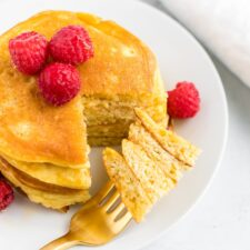 Stack of coconut flour pancakes topped with raspberries. A fork has taken a bite out of the stack.
