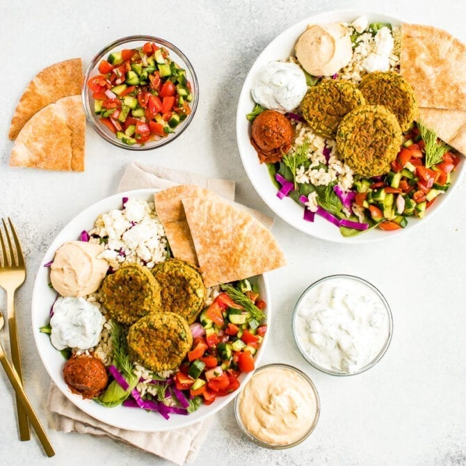 two falafel bowls on a table surrounded by cucumber tomato salad in a bowl, dips and pita.