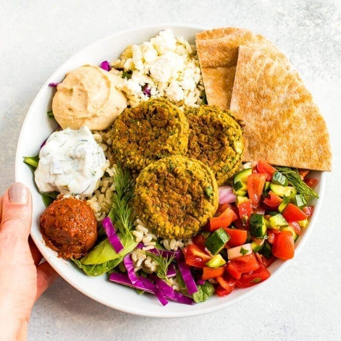 Hand holding a bowl of mixed greens and brown rice topped with Mediterranean dips, feta, pita and baked falafel.