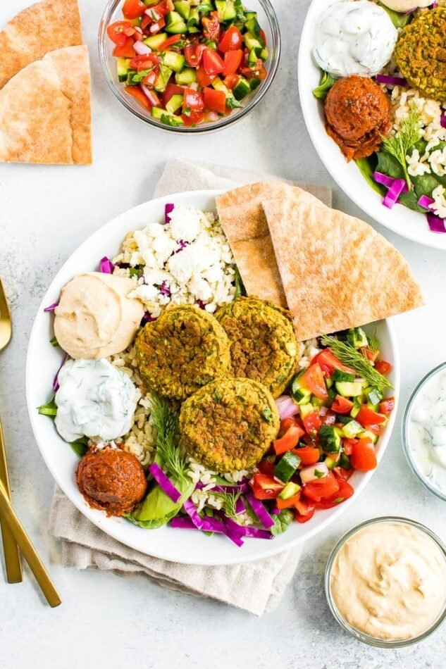 Falafel bowl on a table surrounded by cucumber tomato salad in a bowl, dips and pita.