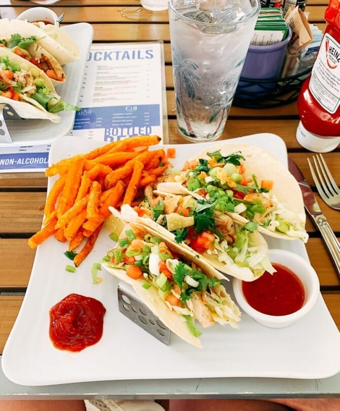 Plate of fish tacos with sweet potato fries.