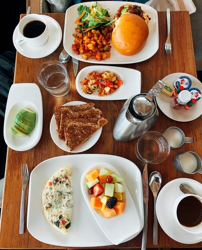 Restaurant table full of breakfast food-- breakfast sandwiches, hash, toast, eggs, and fruit.