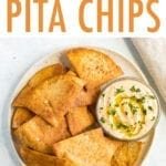 Baked pita chips on a plate with a bowl of hummus.