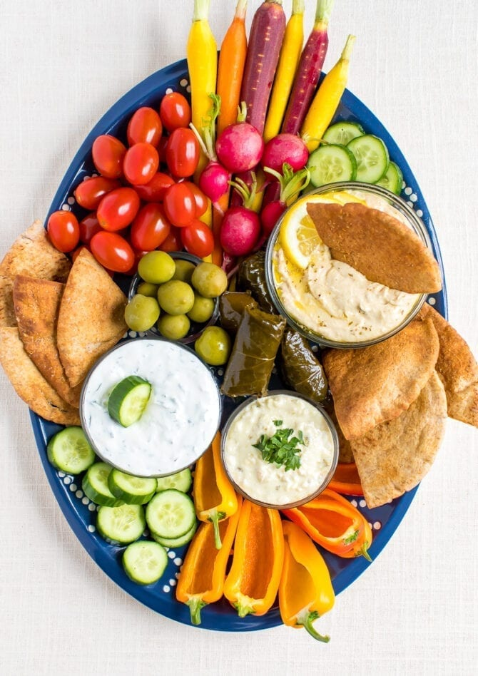 Vegetarian mezze platter with carrots, radishes, tomatoes, cucumber slices, green olives, domades, pita chips, peppers and a variety of hummus and dips.