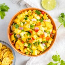 Bowl of pineapple salsa next to a bowl of plantain chips, cilantro sprigs and a slice of lime.