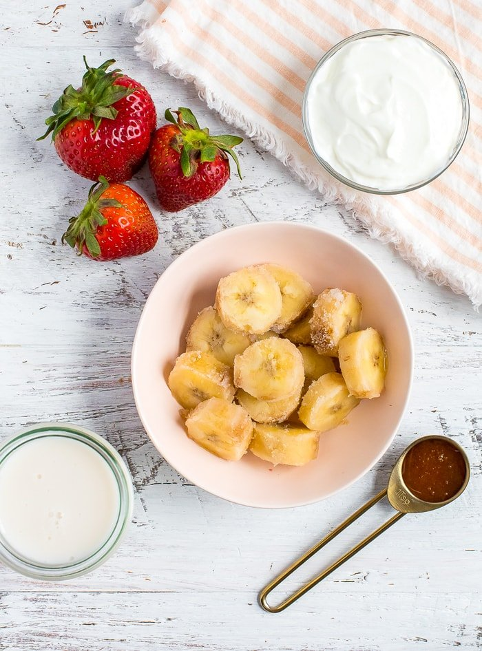 Ingredients to make a healthy strawberry banana smoothie. Fresh strawberries, a bowl of sliced frozen banana, a bowl of greek yogurt, a teaspoon of honey, and a jar of almond milk.