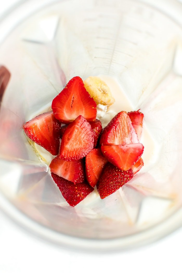 Strawberries, frozen banana, almond milk, honey, and greek yogurt in a blender.