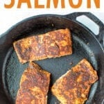 Three pieces of blackened salmon in a cast iron skillet.