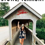 Woman standing and waving under a covered bridge that has a Stowe Vermont sign on the top.