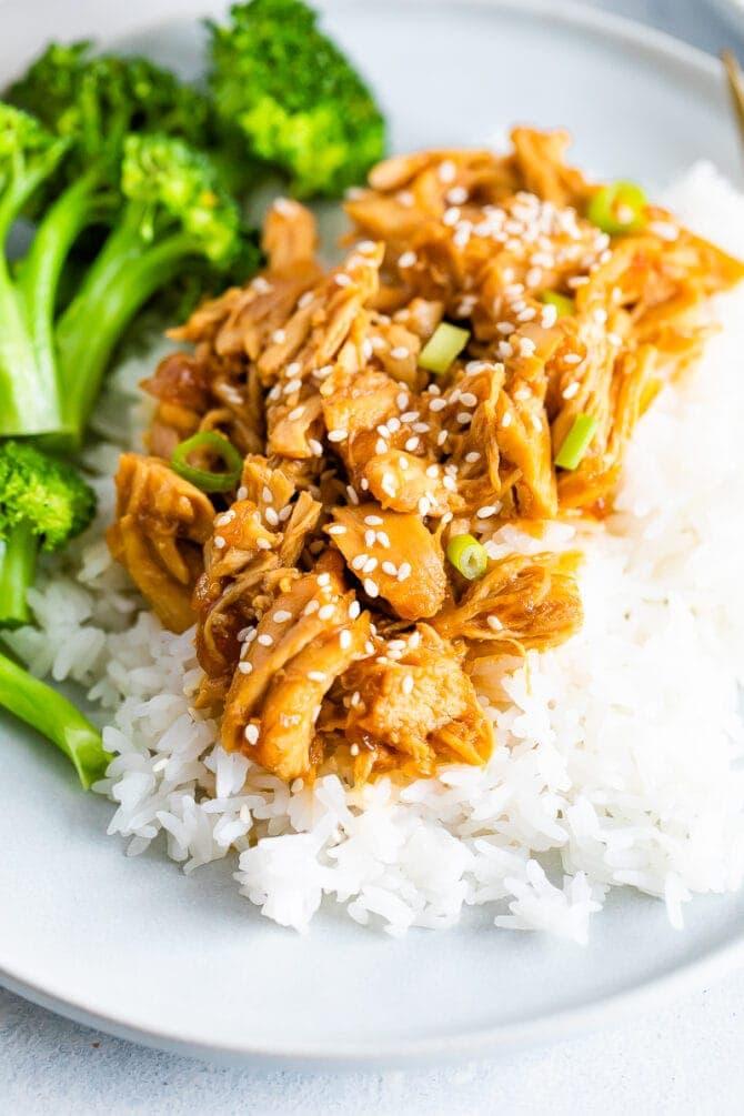 Assiette avec brocoli, riz et poulet teriyaki râpé garni d'oignons verts.