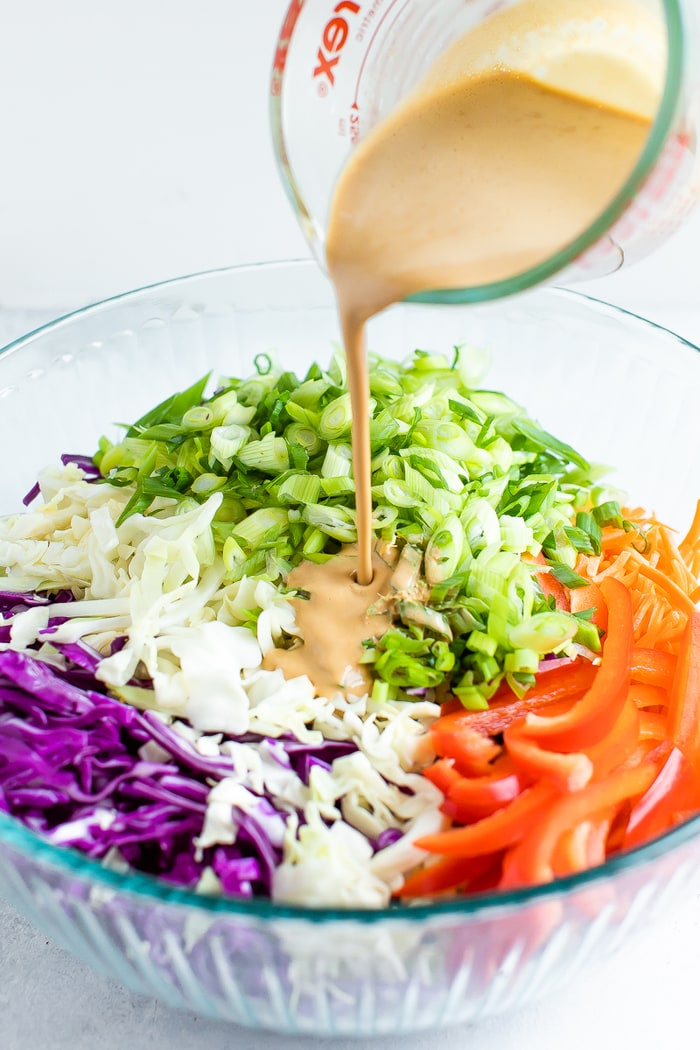 Asian dressing being poured into a bowl of the ingredients for an asian slaw before being tossed. Ingredients in the bowl are cabbage, scallions, carrots, and peppers.