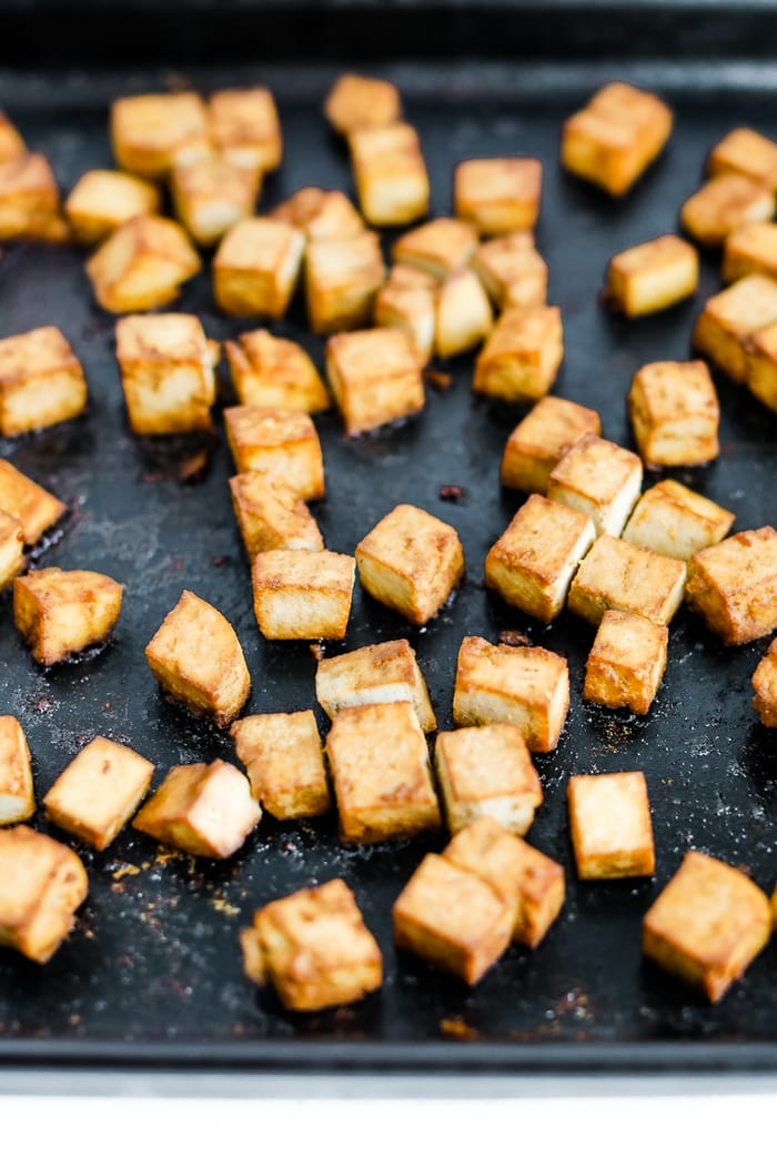 Crispy baked tofu on a sheet pan with some teriyaki sauce.