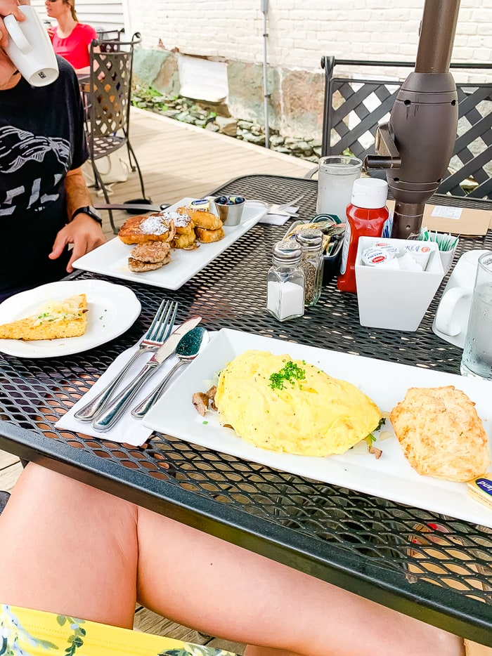 Outdoor table at a restaurant with plates of breakfast food.