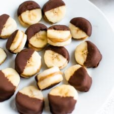 Chocolate peanut butter banana bites on a plate. Slices of banana sandwiched with peanut butter and dipped half in chocolate and frozen.