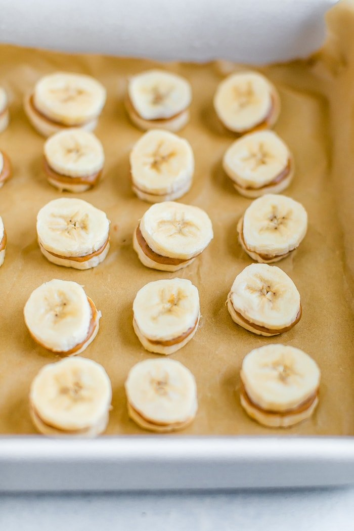 Slices of banana sandwiched with peanut butter on a tray lined with parchment paper.