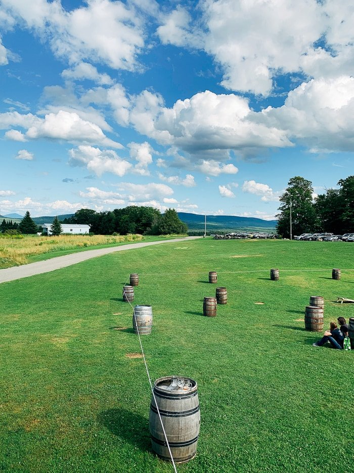 View of a brewery with open land, barrels, and trees and mountains in view.