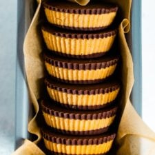 Stack of homemade peanut butter cups in parchment paper, in a bundt pan.