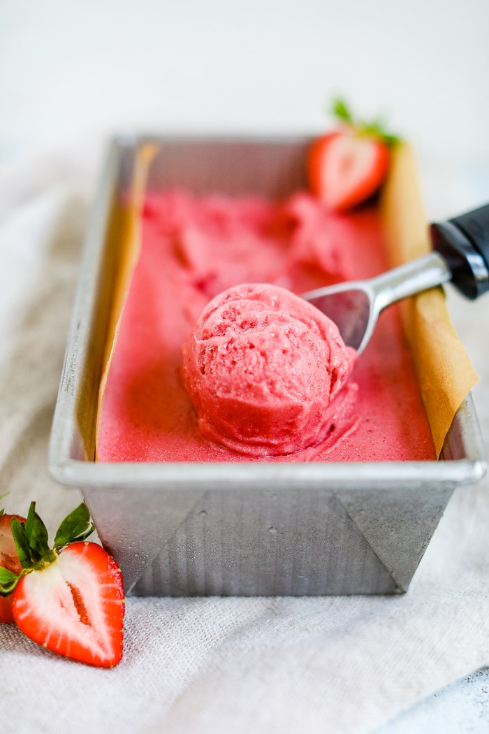 A ice cream scooper scooping strawberry coconut sorbet.