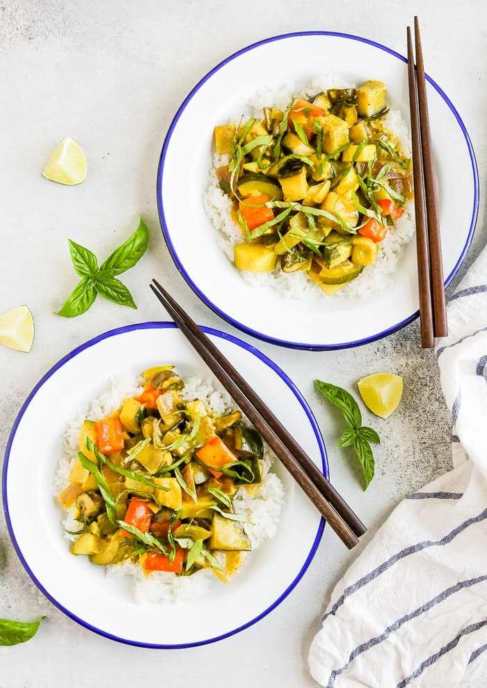 Two plates with summer vegetable coconut curry served over rice. Topped with basil and chop sticks are on the side of the plates. Fresh basil and limes are around the two plates.