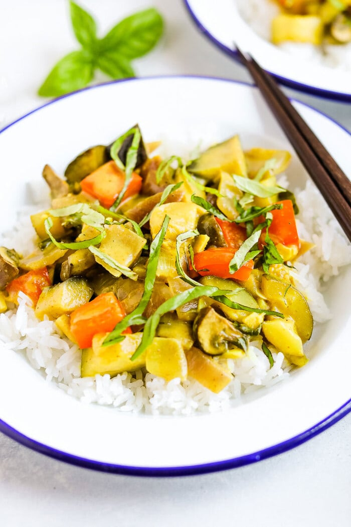 Summer vegetable curry served over rice and topped with fresh basil.