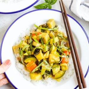 Hand holding a plate of summer vegetable coconut curry served over rice and topped with basil. Two chop sticks are on the side of the bowl.