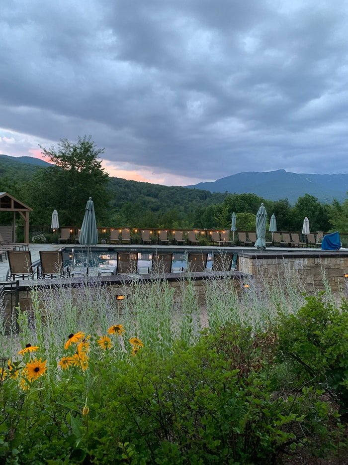 View of a resort pool in Stowe, Vermont. The pool has a wild flower garden and a view of the mountains.