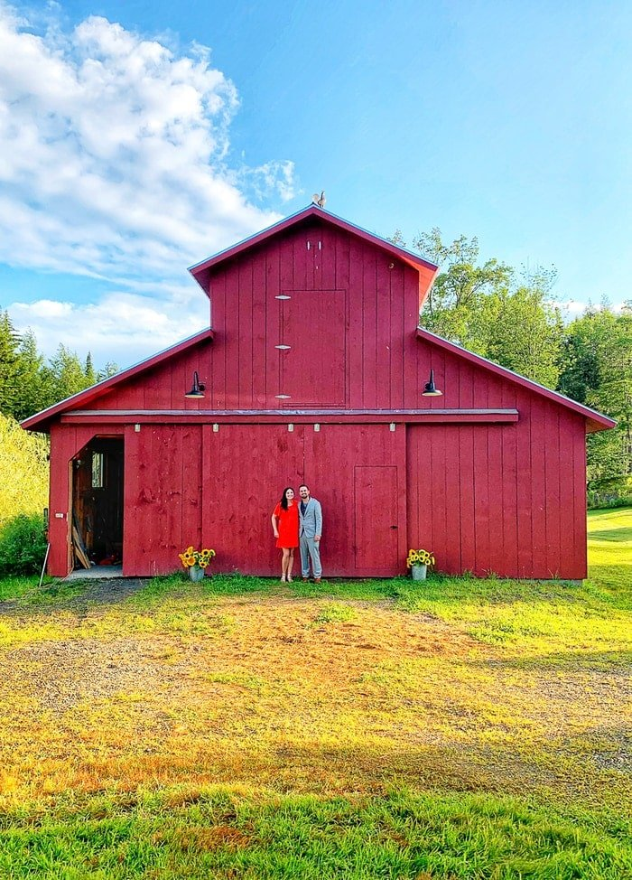 Couple standing in front of a red barn.