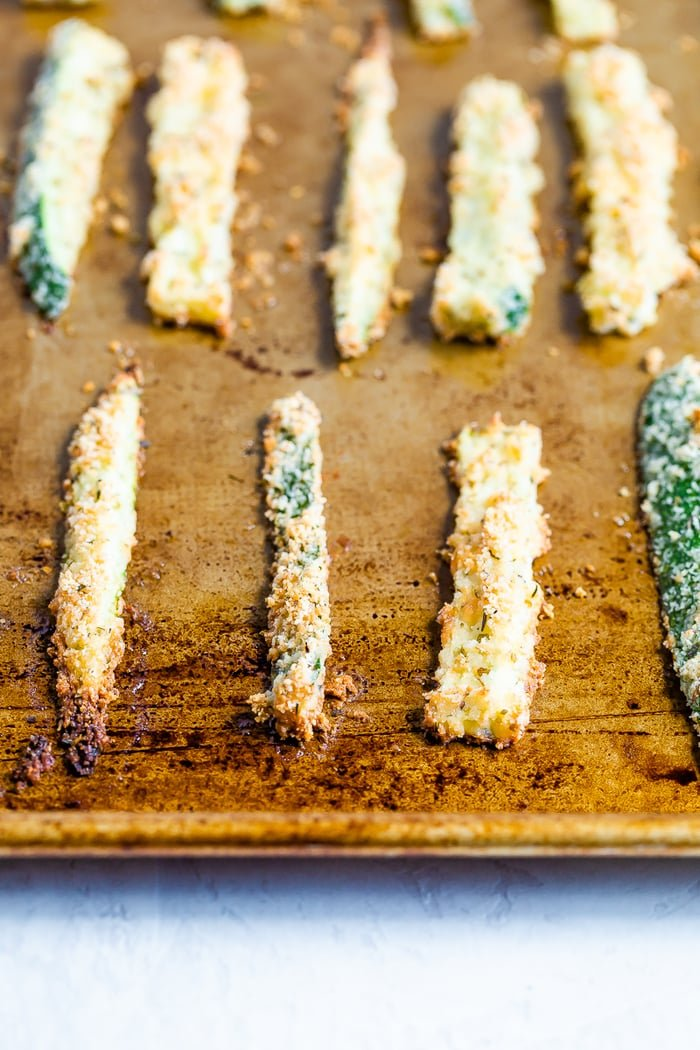 Sheet pan with crispy baked zucchini fries lined up on the sheet.