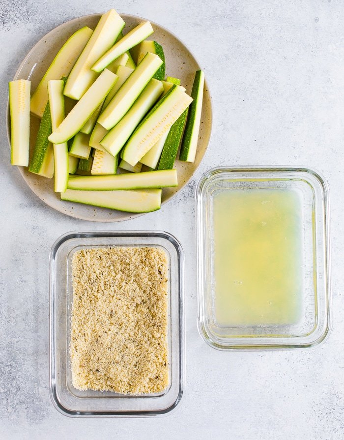 Staged ingredients for making baked zucchini fries: a plate of chopped zucchini, a dish with almond flour and parmesan coating, and a container with egg whites.