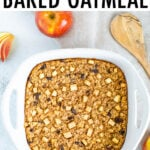 Dish of apple cinnamon baked oatmeal filled with raisins and chunks of apples. Apples and a wooden spoon are around the dish.