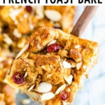 A slice of french toast bake on a wooden spoon with a casserole dish of the french toast back in the background. Bake is topped with cranberries and almond slices.