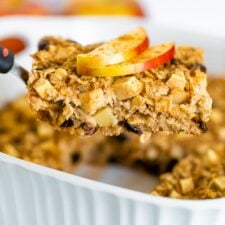 Spatula lifting a slice of apple cinnamon baked oatmeal from a baking dish. Oatmeal topped with apple slices and cinnamon.