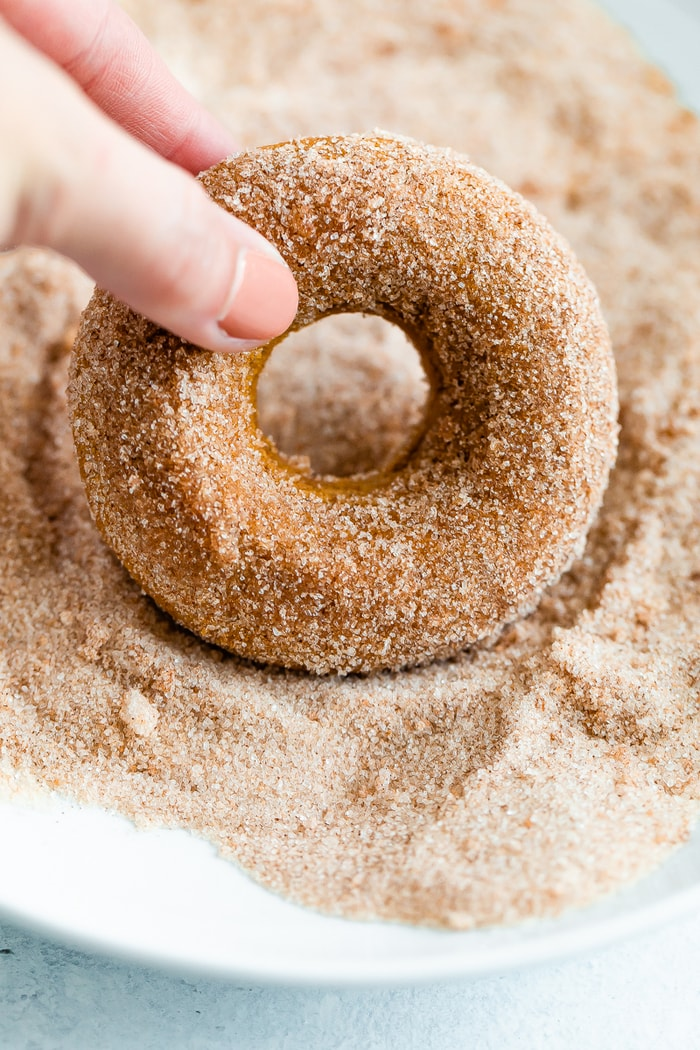 Hand dipping an apple cider donut into cinnamon sugar.