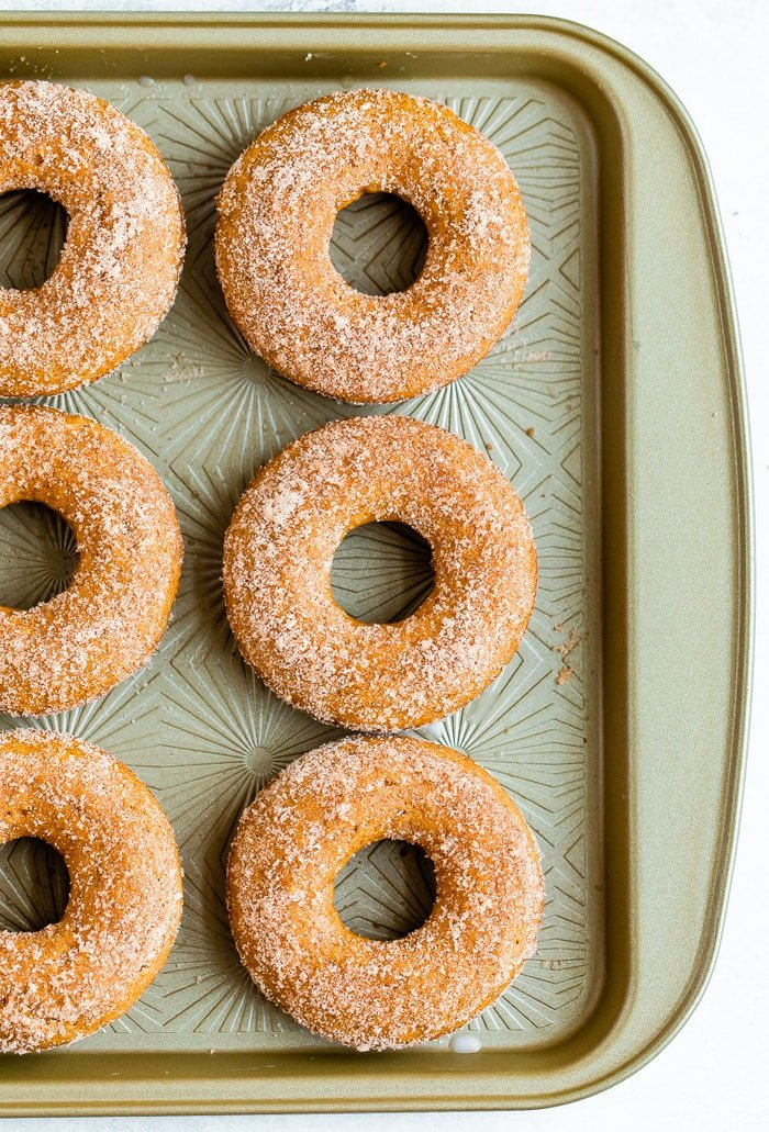 Cookie sheet with baked apple cider donuts on it.