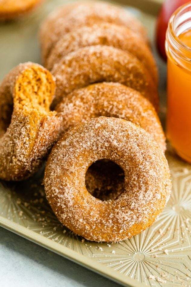 Apple cider donuts on a tray. One had a bit taken out of it, and a mason jar of cider is beside the donuts.
