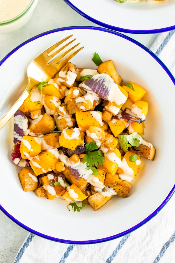 Bowl of roasted butternut squash, tofu, chickpeas, and onion topped with cilantro and tahini sauce. A gold fork is on the side of the bowl.