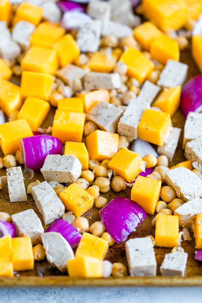 Uncooked chunks of butternut squash, tofu, chickpeas, and onions on a sheet pan.