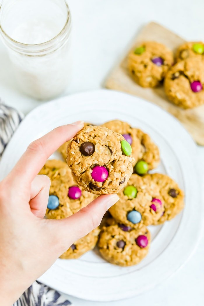 Hand holding a gluten-free peanut butter monster cookies with a plate of cookies in the background and a glass of milk. Oats and colored chocolate candies are in the cookies.