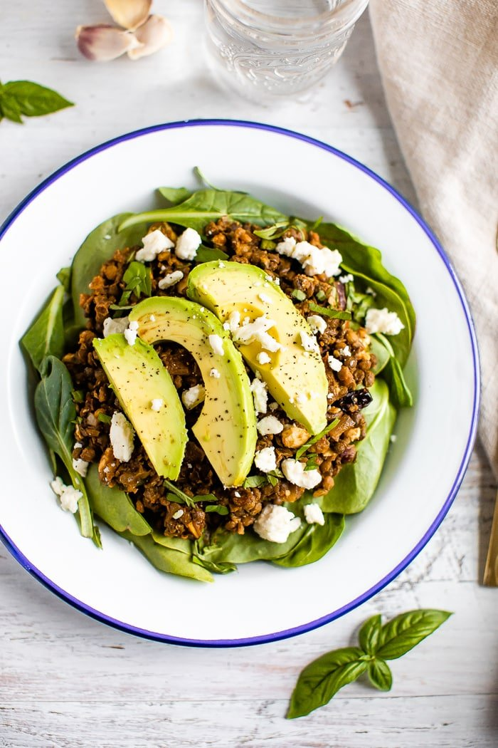 Plate with a bed of fresh spinach topped with a warm Mediterranean salad, topped with feta and avocado.