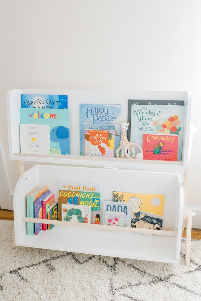 White and wood modern nursery bookshelf with children's books and toys.