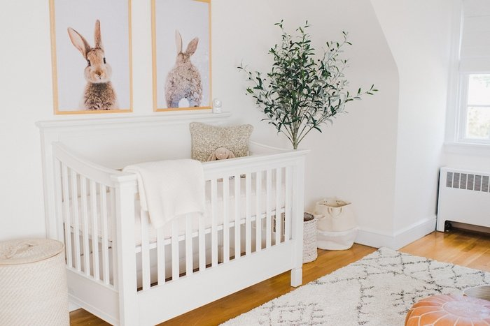 Baby girl neutral nursery with bunny prints above crib.