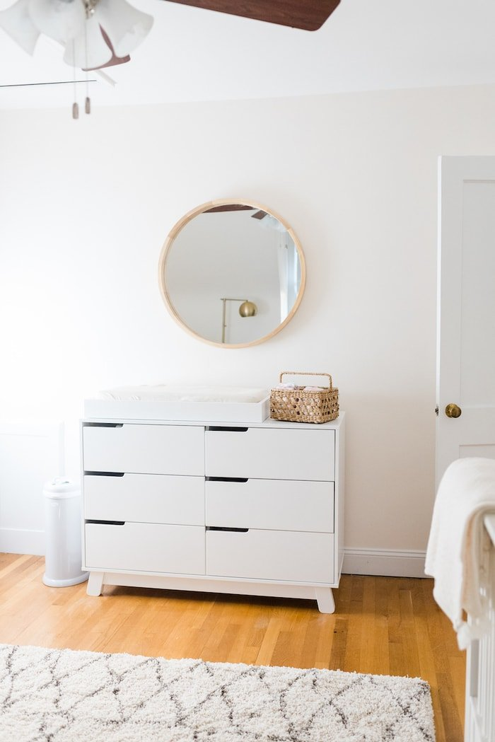 Baby girl nursery with a white dresser changing station and round mirror above.