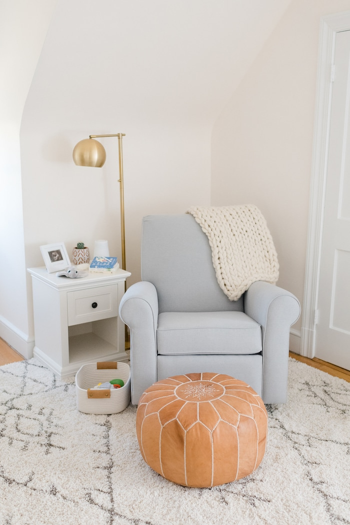 Baby girl nursery with a blue gray glider, gold flour lamp and leather pouf.