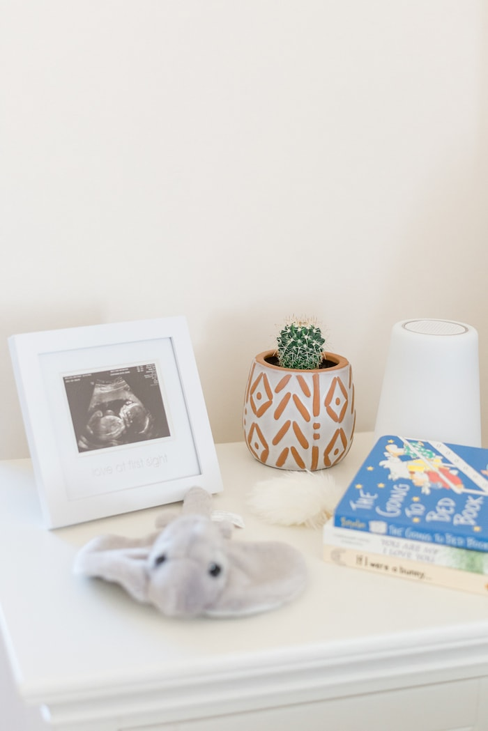 Nightstand in a nursery with sonogram photo, mini cactus, noise machine, stuffed stingray and books.
