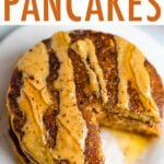Stack of pumpkin pancakes, drizzled with peanut butter and maple syrup, with a bite taken out of the stack.