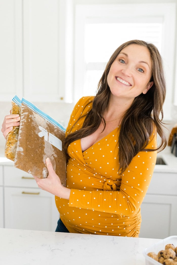 Pregnant woman holding homemade frozen meal prep meals.