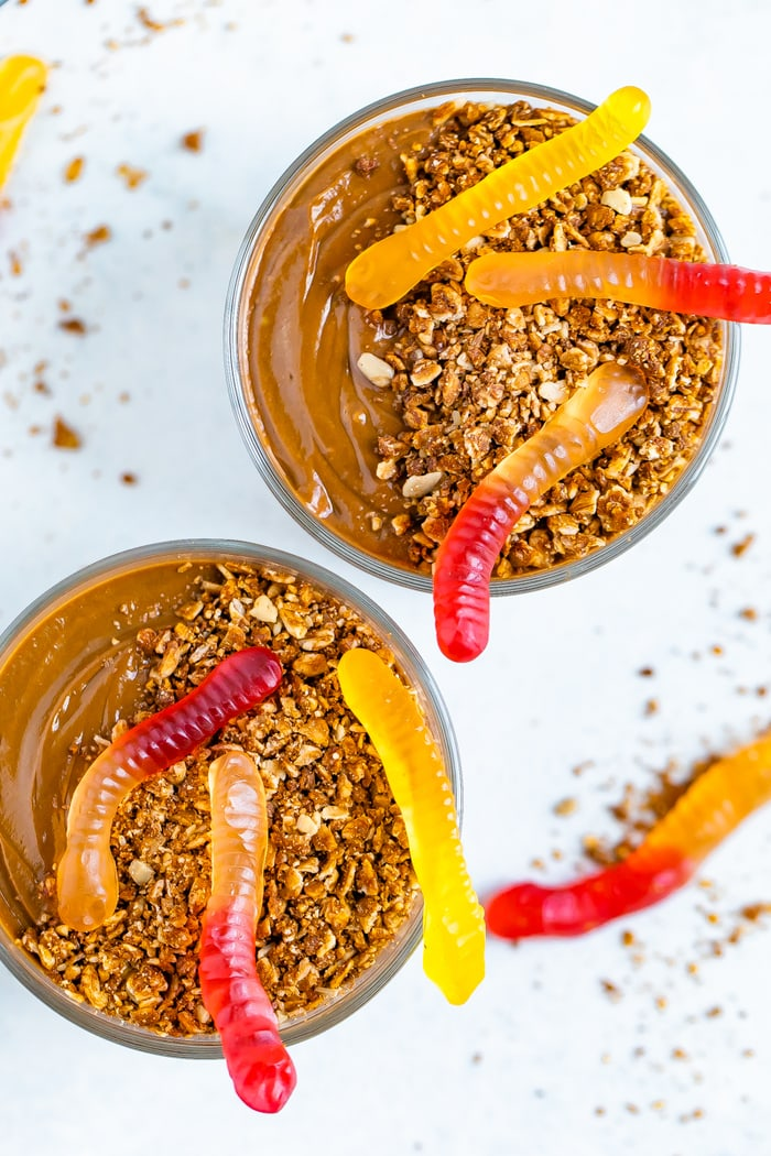 Two dirt pudding cups topped with granola and gummy worms.