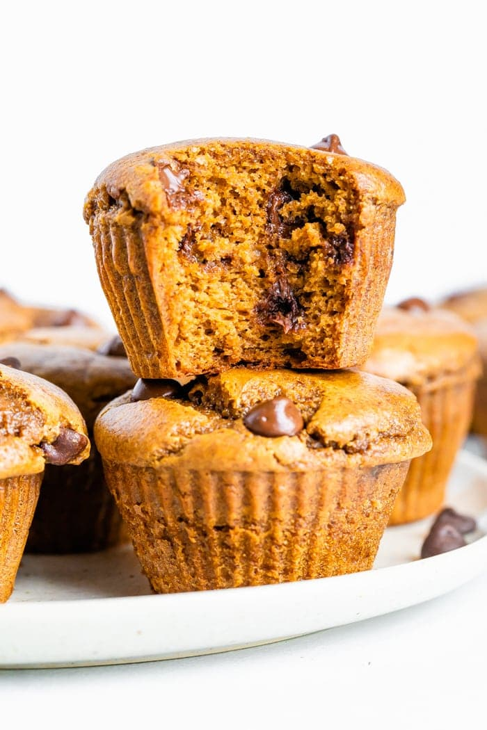 Two healthy pumpkin muffins stacked with a bite taken out of the top muffin.