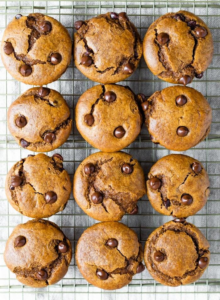 An overhead shot of a cooling rack with 12 flourless pumpkin muffins on top.
