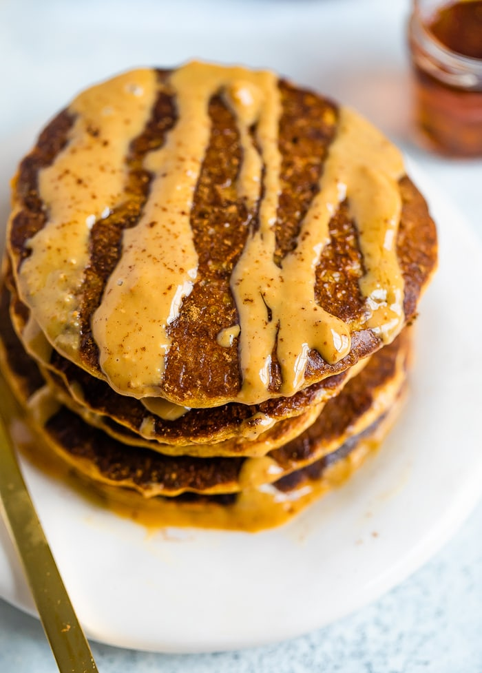 Stack of healthy pumpkin pancakes drizzled with peanut butter. A jar of maple syrup is beside the pancakes.